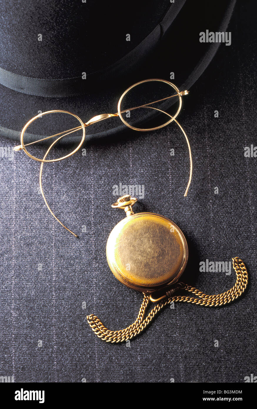 Humorous English face, conceptual still life with bowler hat, reading glasses, pocket watch, chain, on pinstripe - Stock Image