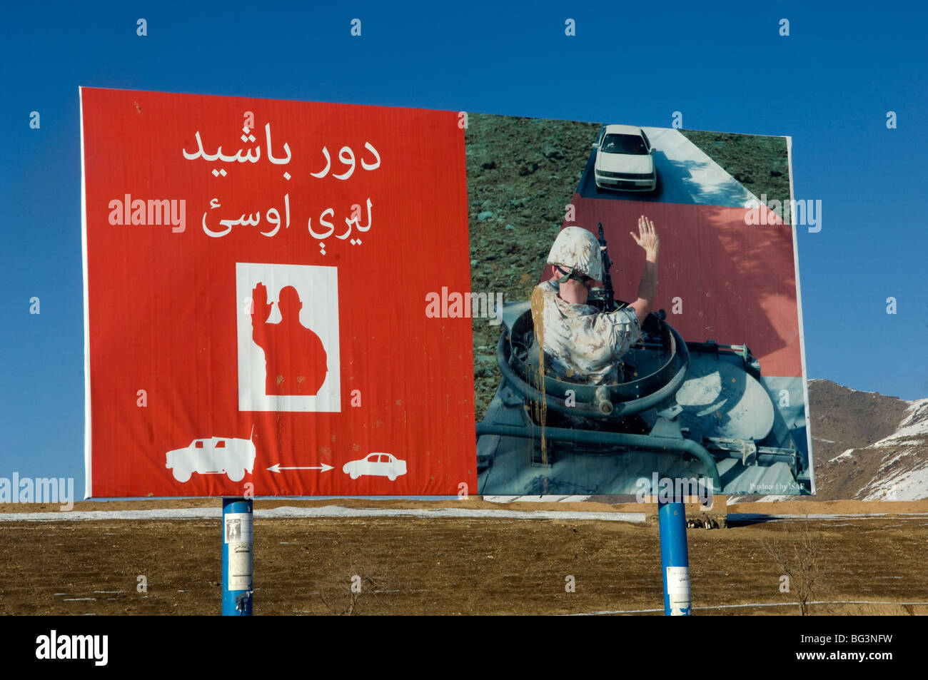 Afghan woman in burka walks past an ISAF military stop sign in Kabul city, Afghanistan. - Stock Image