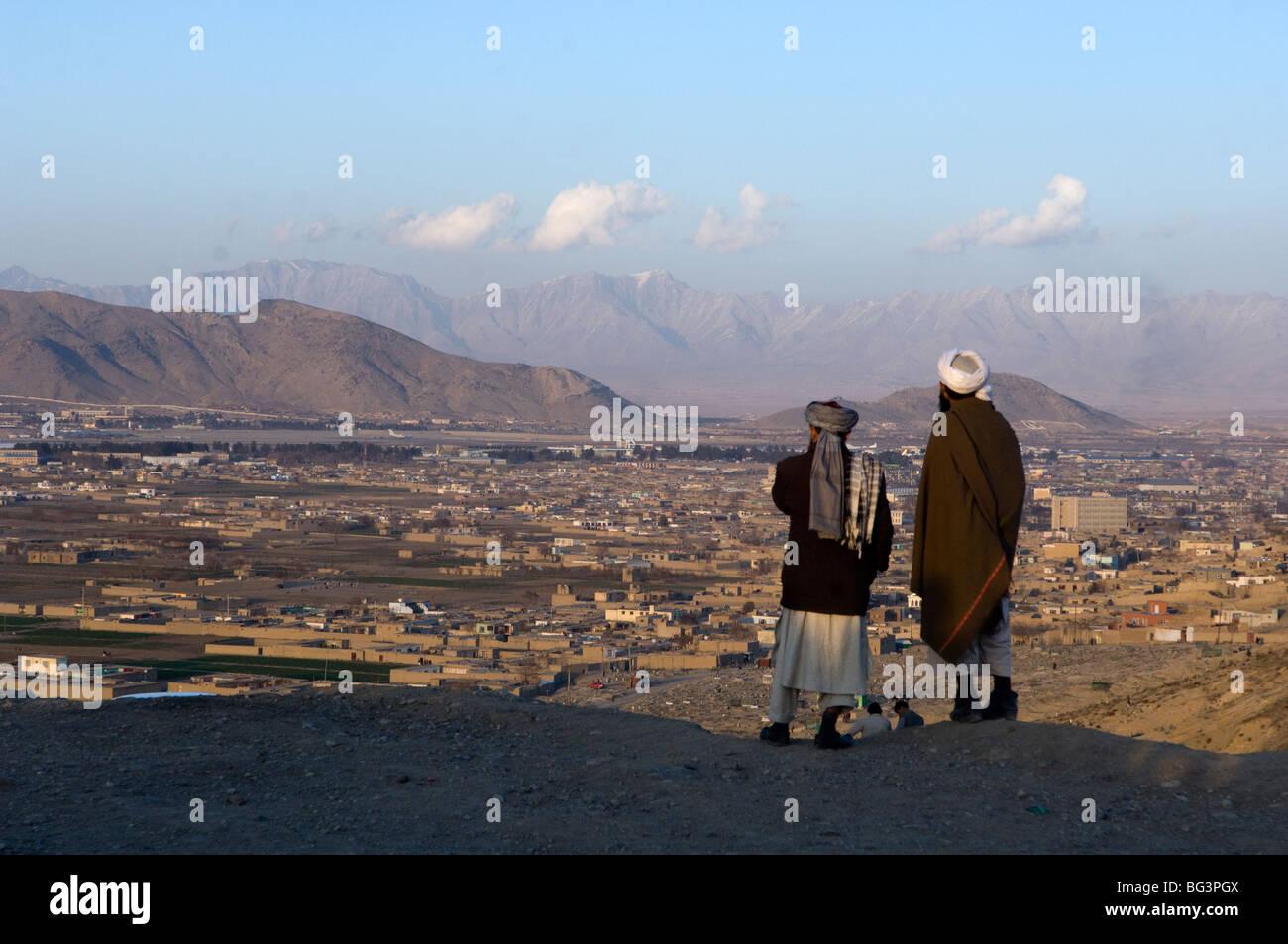 Afghan men look toward Kabul city, Afghanistan. - Stock Image