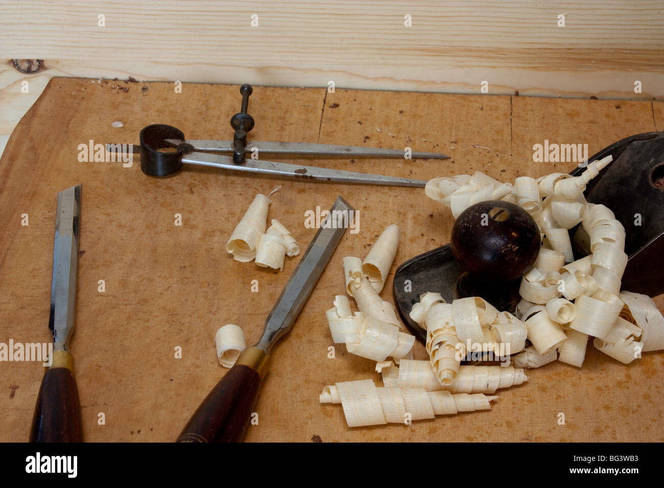 Dividers Skew chisels and a plane with pine shavings - Stock Image