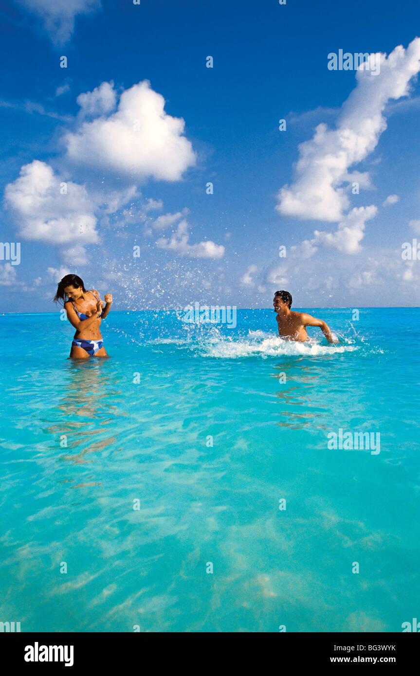 Couple splashing in the sea, Maldives, Indian Ocean, Asia - Stock Image