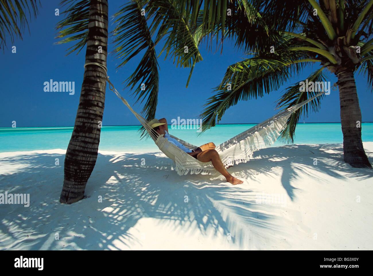 Man relaxing on a beachside hammock, Maldives, Indian Ocean, Asia - Stock Image