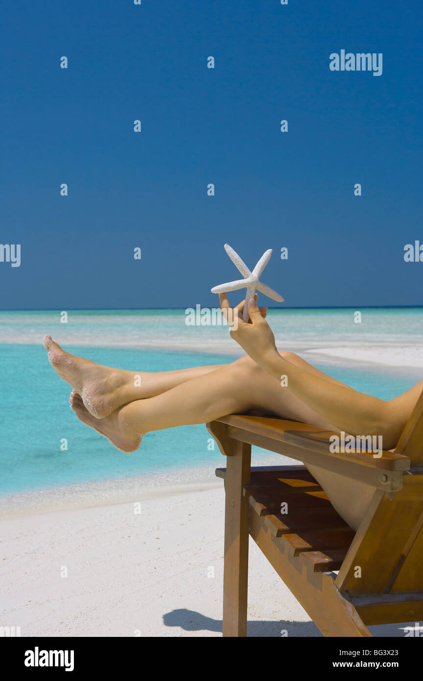 Woman holding seastar on the beach, Maldives, Indian Ocean, Asia - Stock Image