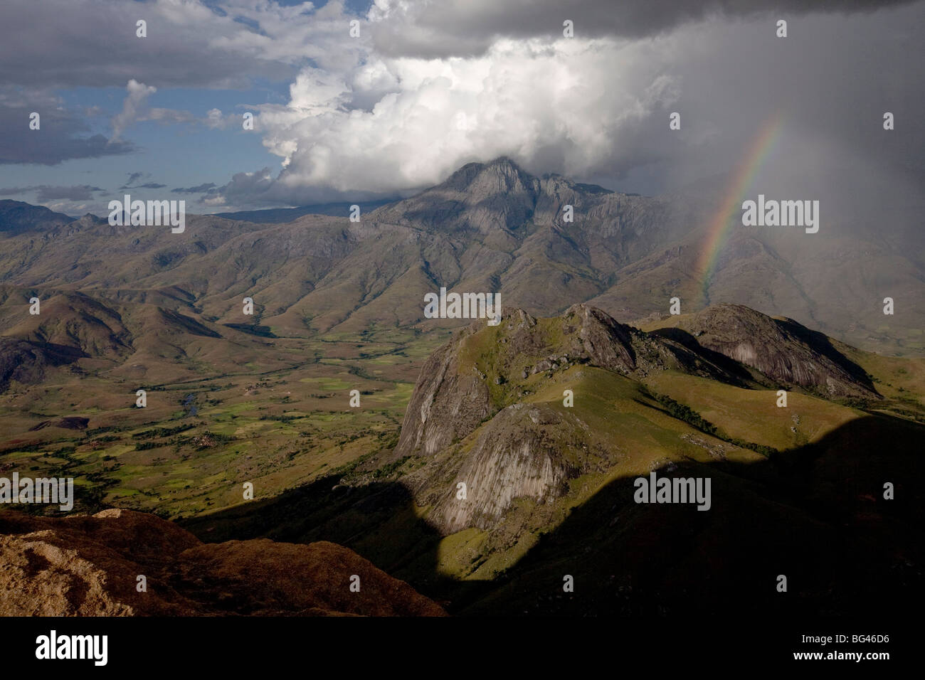 A rainbow appears looking east across the granite mountains of the Andringitra National Park, Southern Madagascar - Stock Image