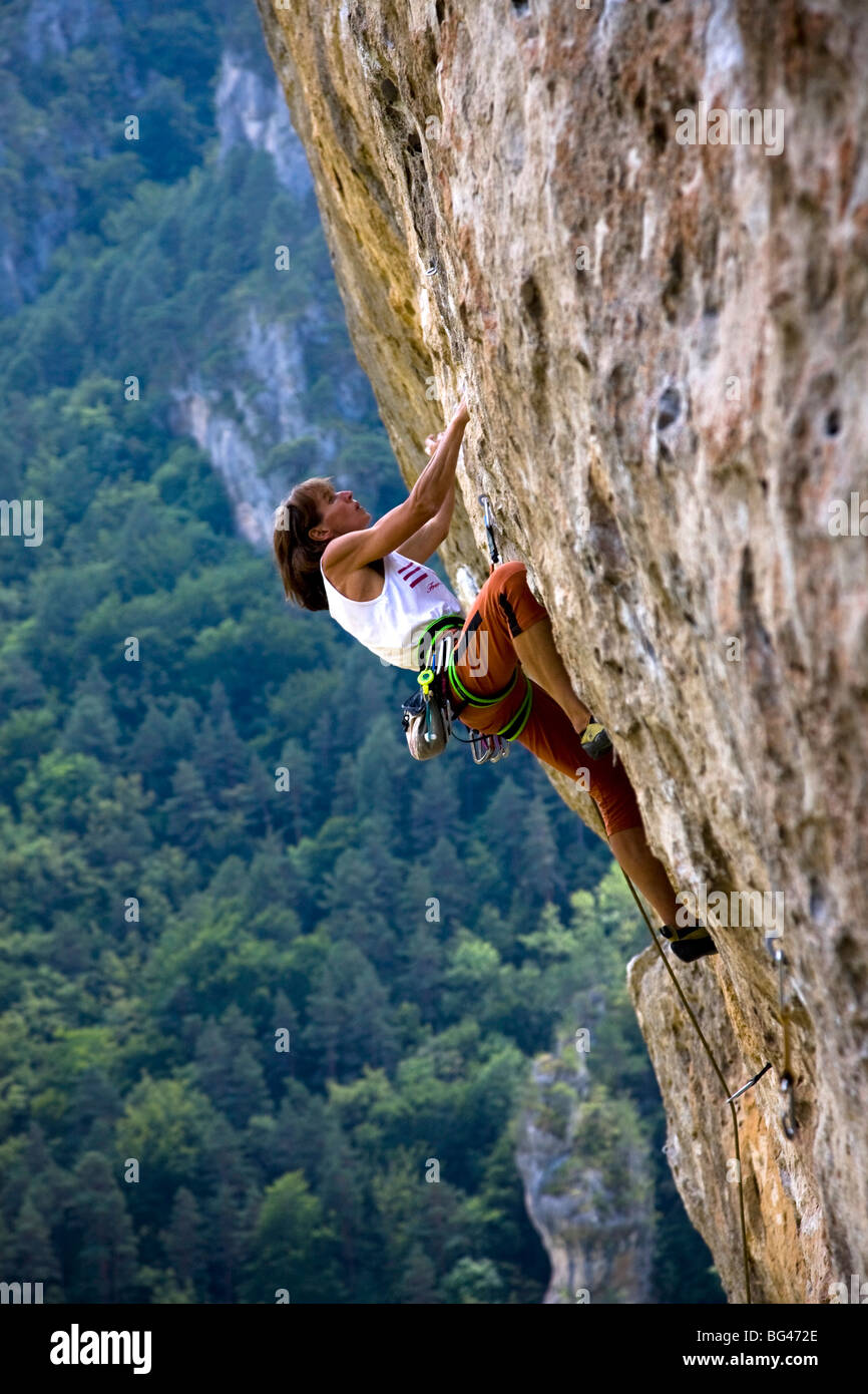 Rock climber tackles overhanging route on limestone cliffs of Gorge du Tarn, Massif Central, near Millau and Rodez, - Stock Image