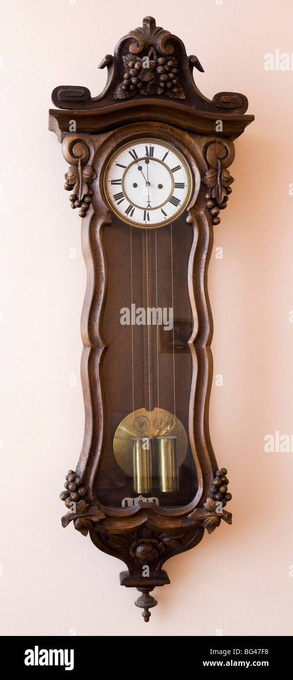 Antique clock hanging on a wall - Stock Image