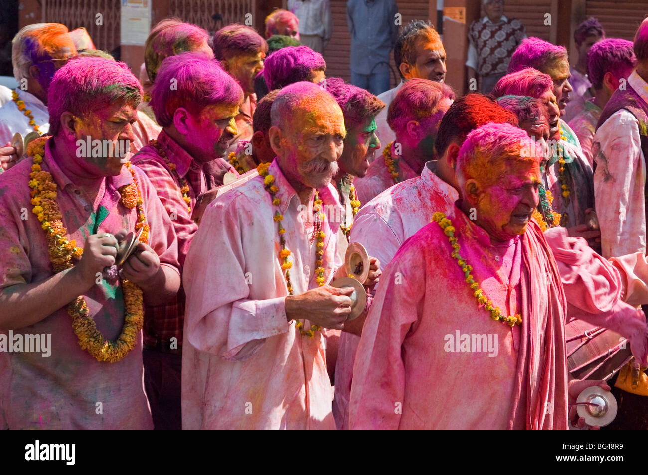 Garlanded men with cymbals in religious procession going to the temple at Holi festival, Jaipur, Rajasthan, India, - Stock Image