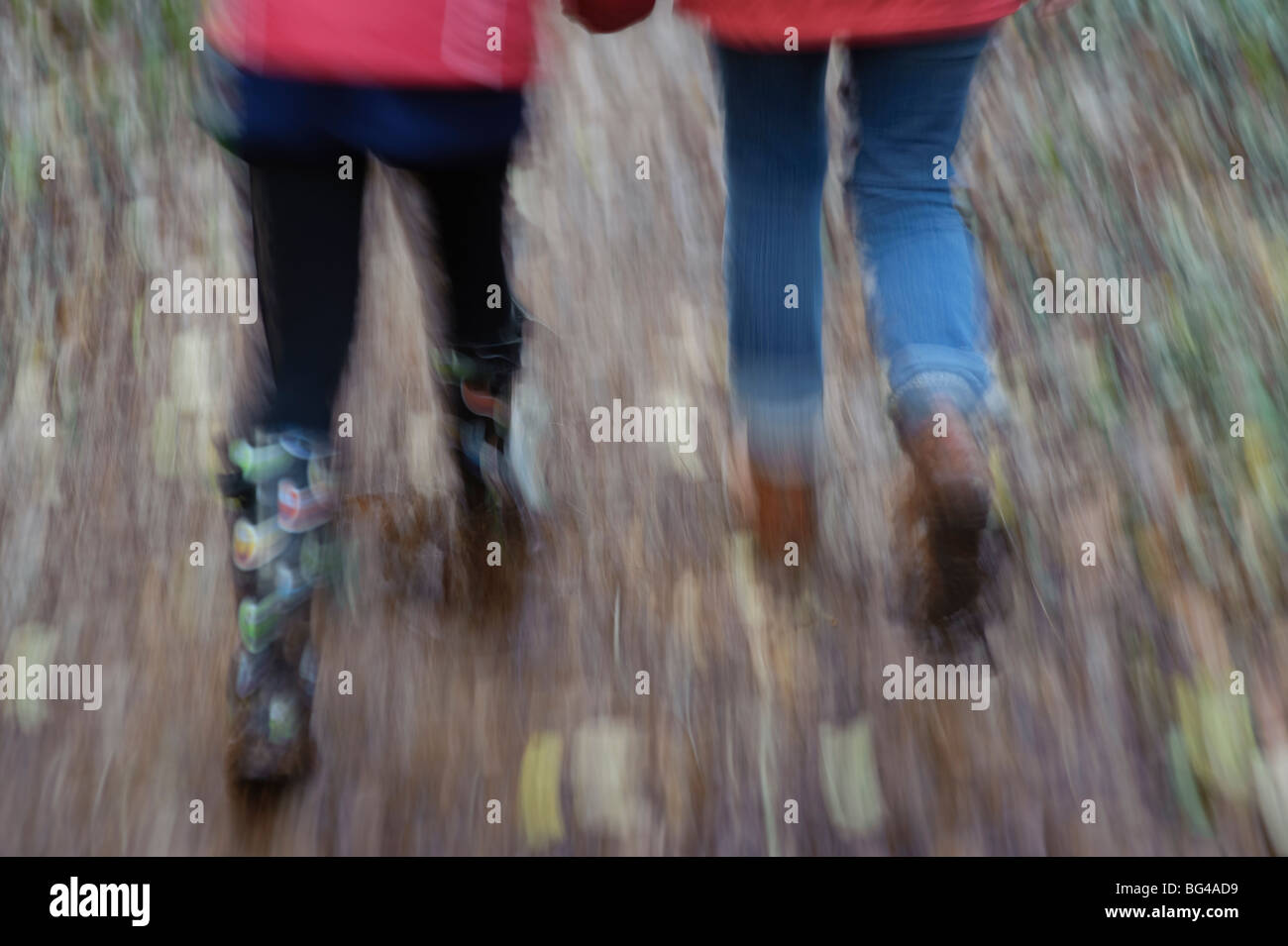 motion blurred image of a mother and her daughter walking in autumn woodland Pembrokeshire Wales UK Stock Photo