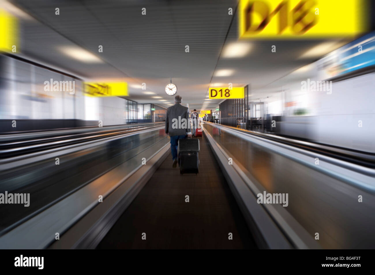 Businessman with luggage on travelator at Schiphol airport, Amsterdam, Netherlands, Europe - Stock Image