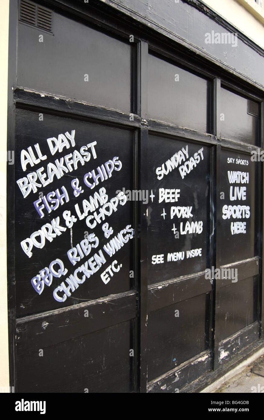 pub food menu chalked onto a wall of a disused pub in shepherds bush, london, england - Stock Image