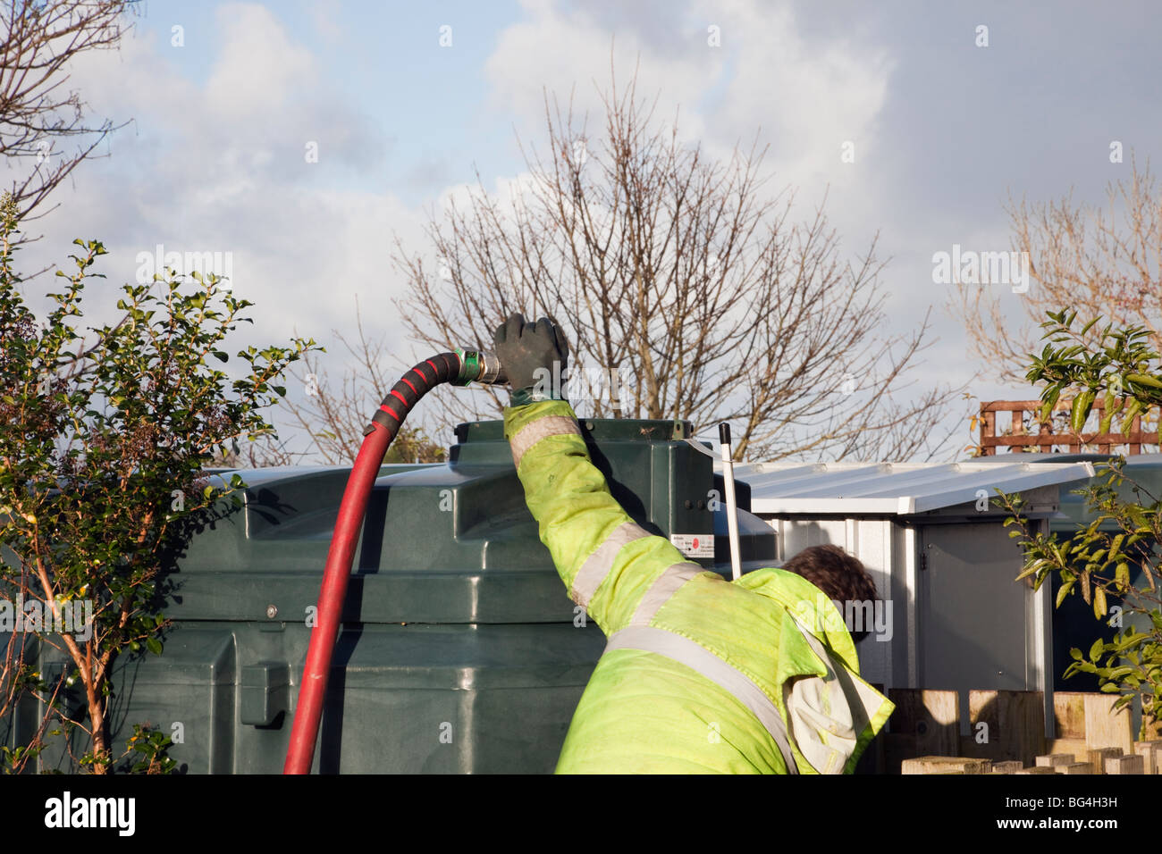 Man filling a domestic oil tank with red supply pipe and nozzle. UK, Britain - Stock Image
