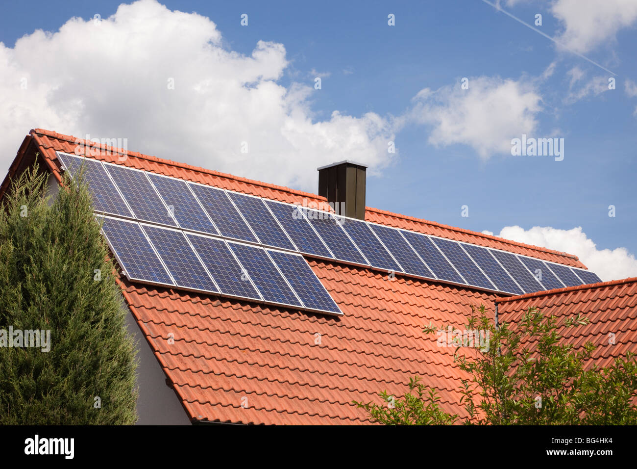 Photovoltaic solar panels on a house roof on a sunny day. Bavaria, Germany, Europe. - Stock Image