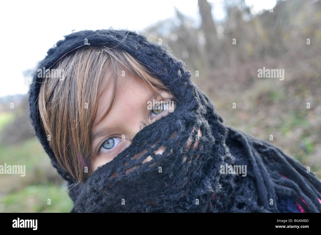 Girl with scarf on her face. - Stock Image