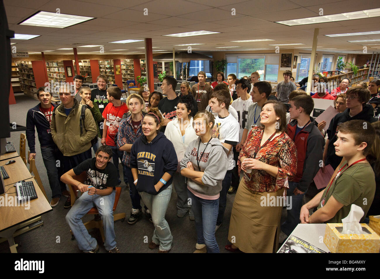 Students Watch Video Announcements on TV in High School Library - Stock Image
