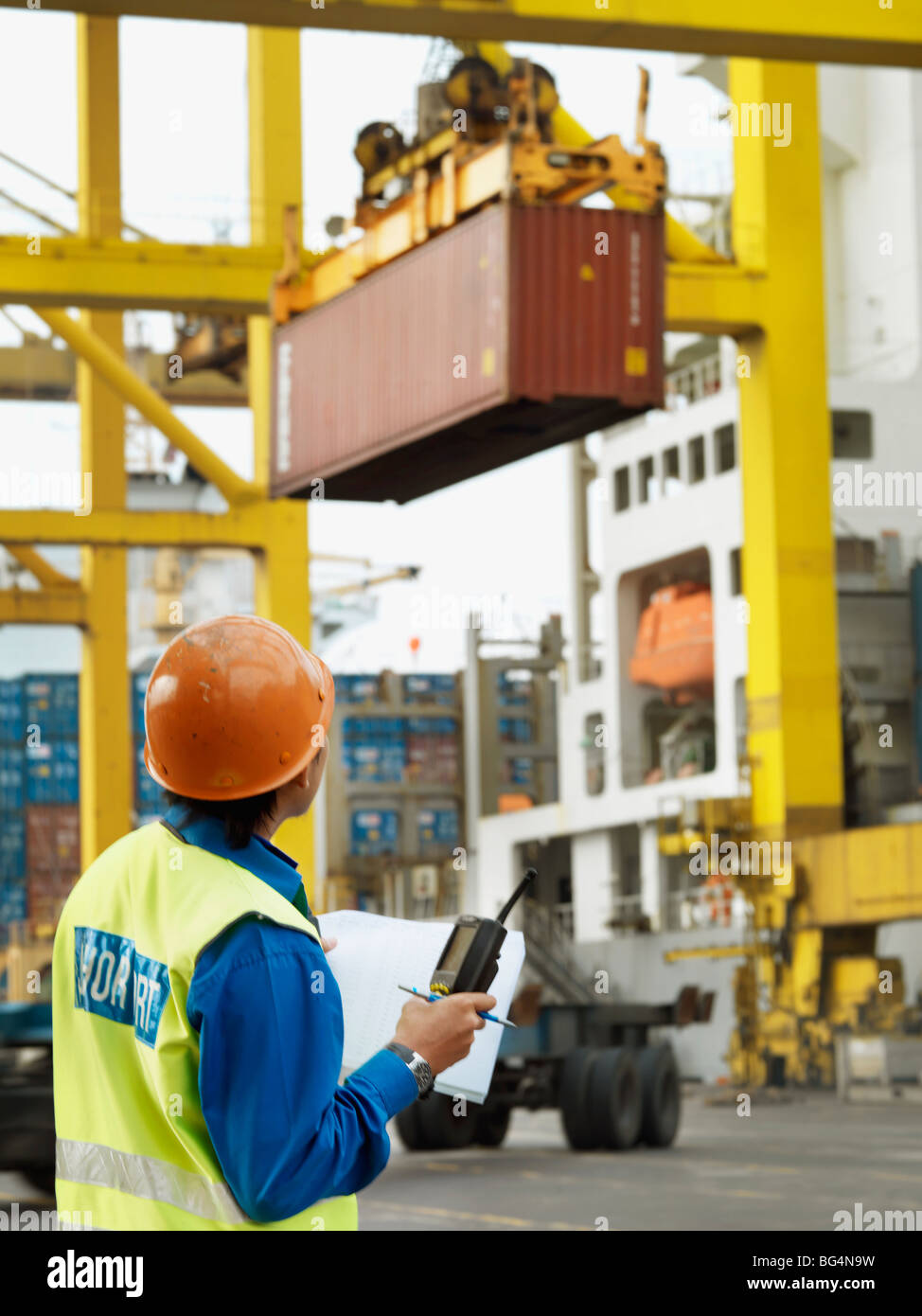 A port worker overseeing a the loading of a ship at a commercial container shipping port. - Stock Image