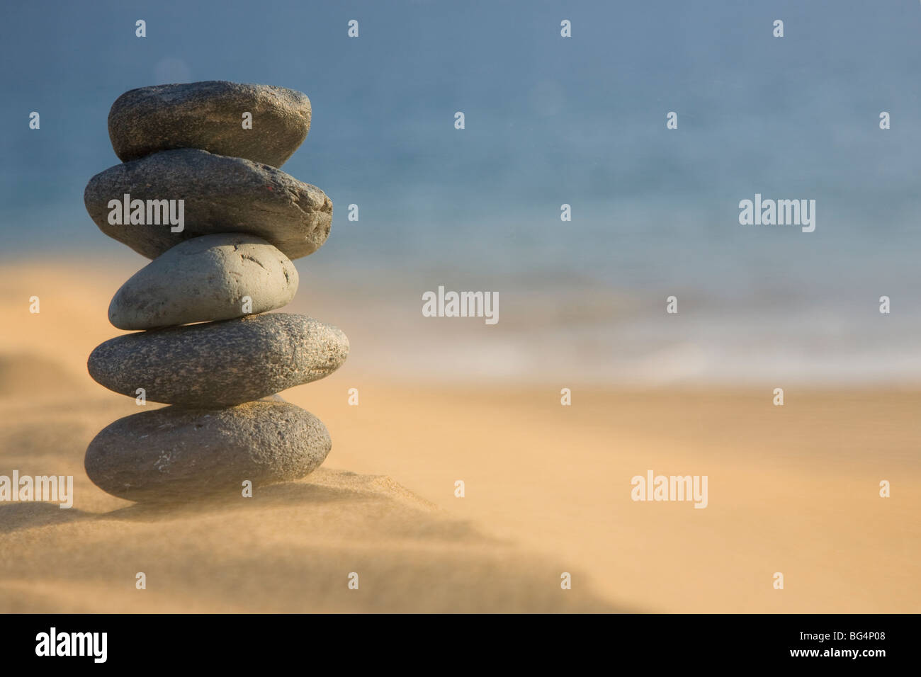 Stack of volcanic pebbles on a Beach with blowing sand - Stock Image