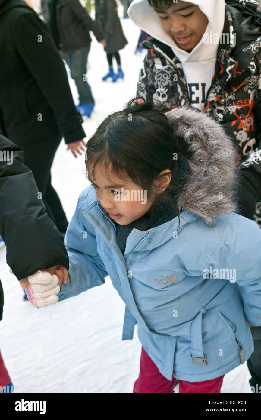 small rosy cheeked Asian girl skater in pale blue parka holding tight to  mom on the free skating rink at Bryant Park New York