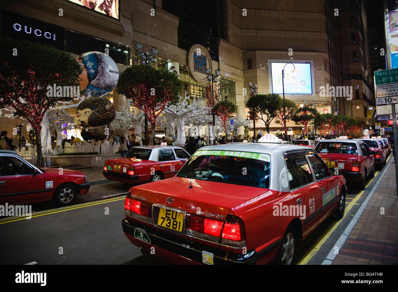 Taxicabs queue up at Times Square shopping mall, Causeway Bay, Hong Kong, China. Christmas season 2008. - Stock Image