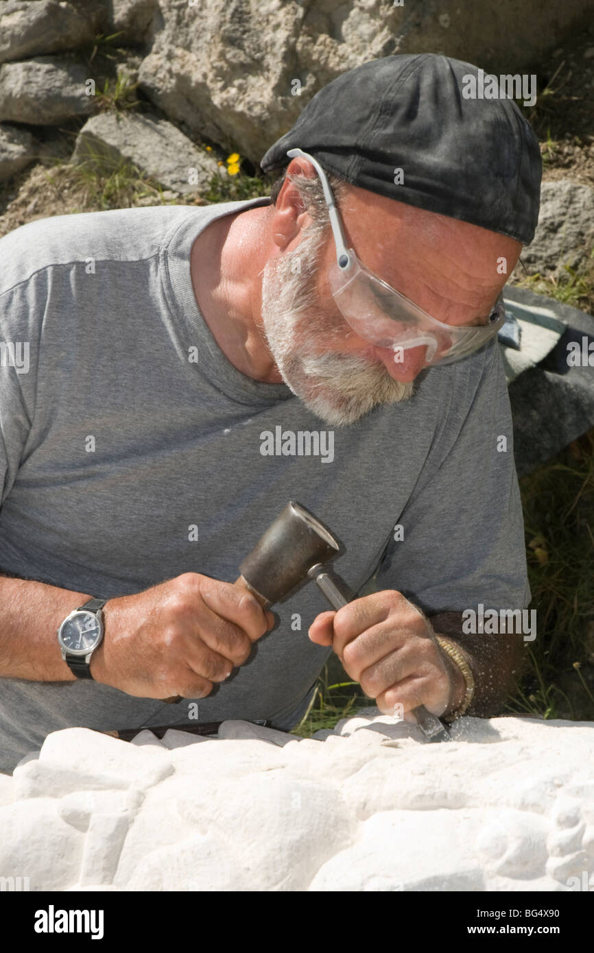 Student at stone cutting course taps away at ancient Portland quarry. - Stock Image