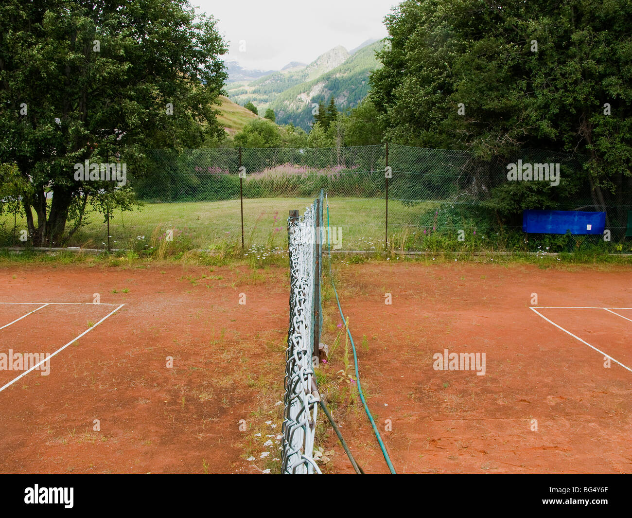 tennis abandonment old neglected abandoned discontinued row rows red earth sports weeds Val D'Aosta Italy Alpes - Stock Image