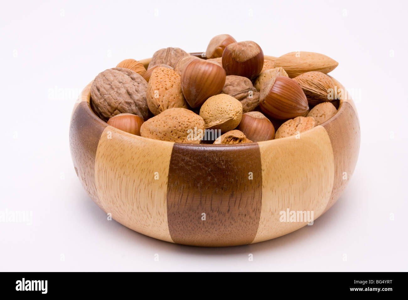wooden bowl filled with mixed nuts in their shells, hazelnuts, walnuts and almonds. - Stock Image
