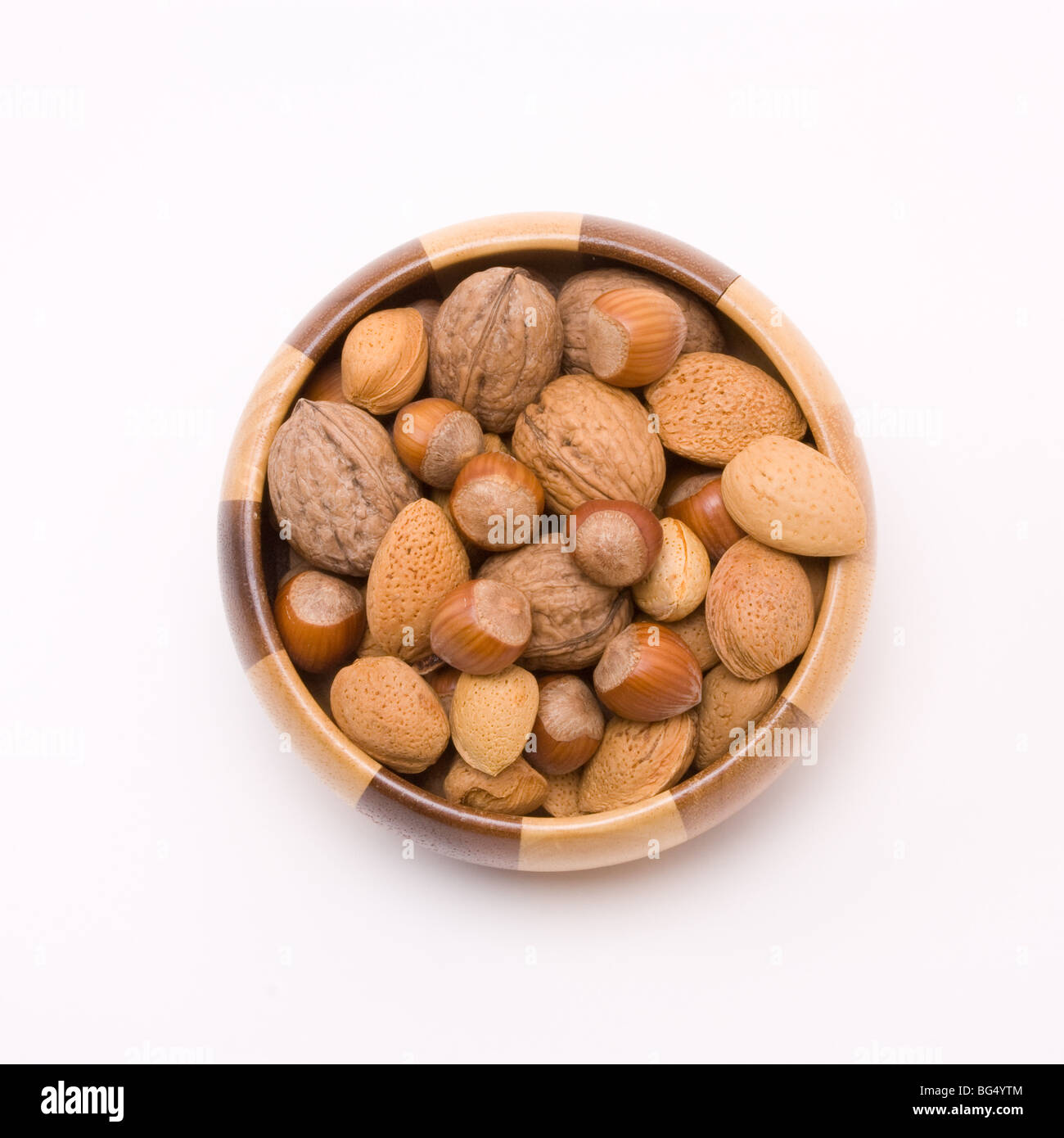 wooden bowl filled with mixed nuts in their shells, hazelnuts, walnuts and almonds. Stock Photo