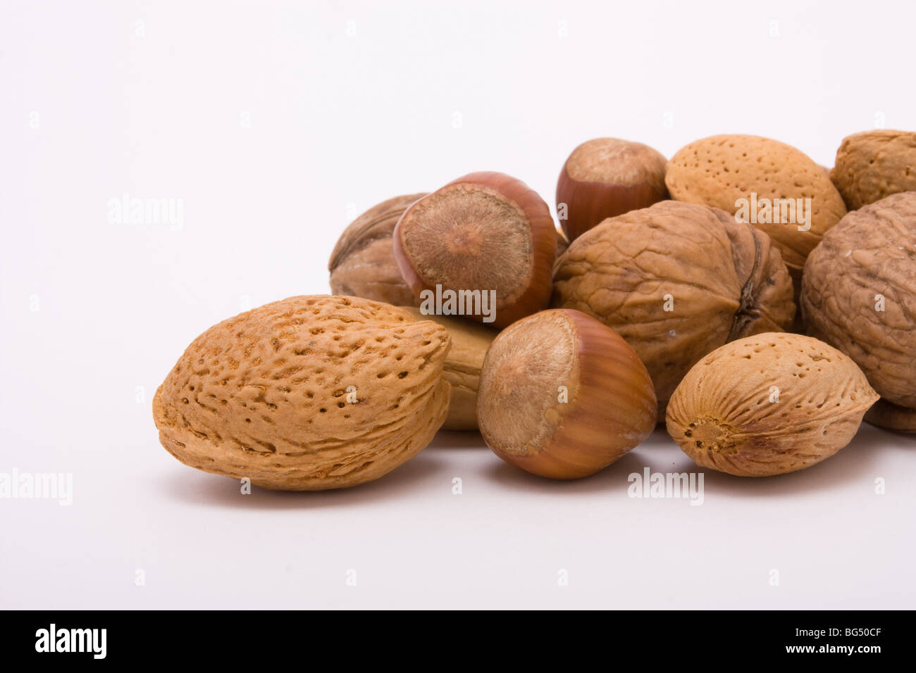 Festive Mixed Nuts of hazelnuts, walnuts and almonds isolated against white background. - Stock Image