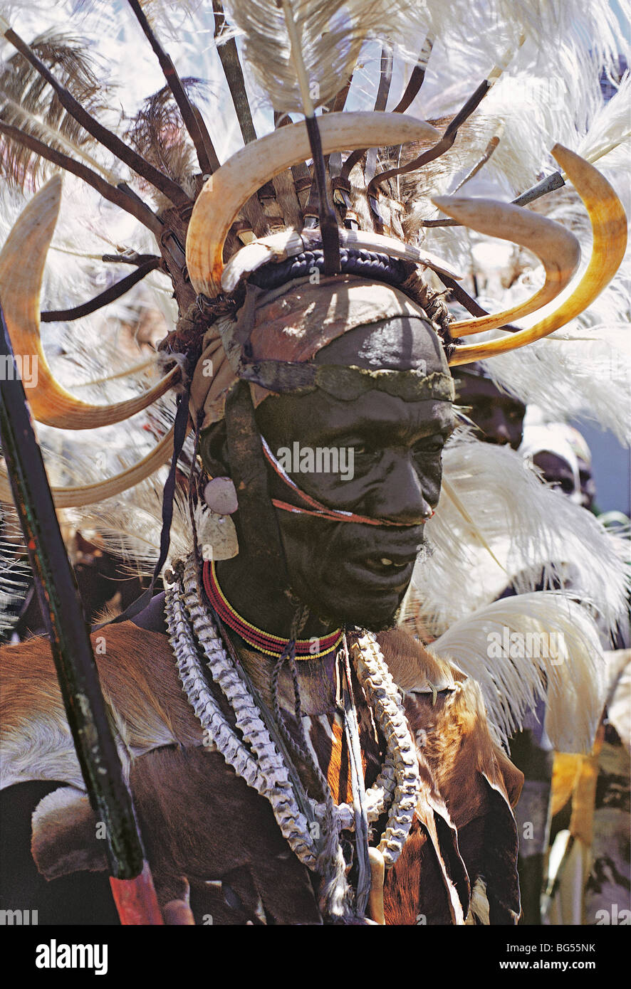 Luo warrior elder with spectacular traditional dress and headdress of ostrich feathers and hippo tusks Kisumu Kenya - Stock Image