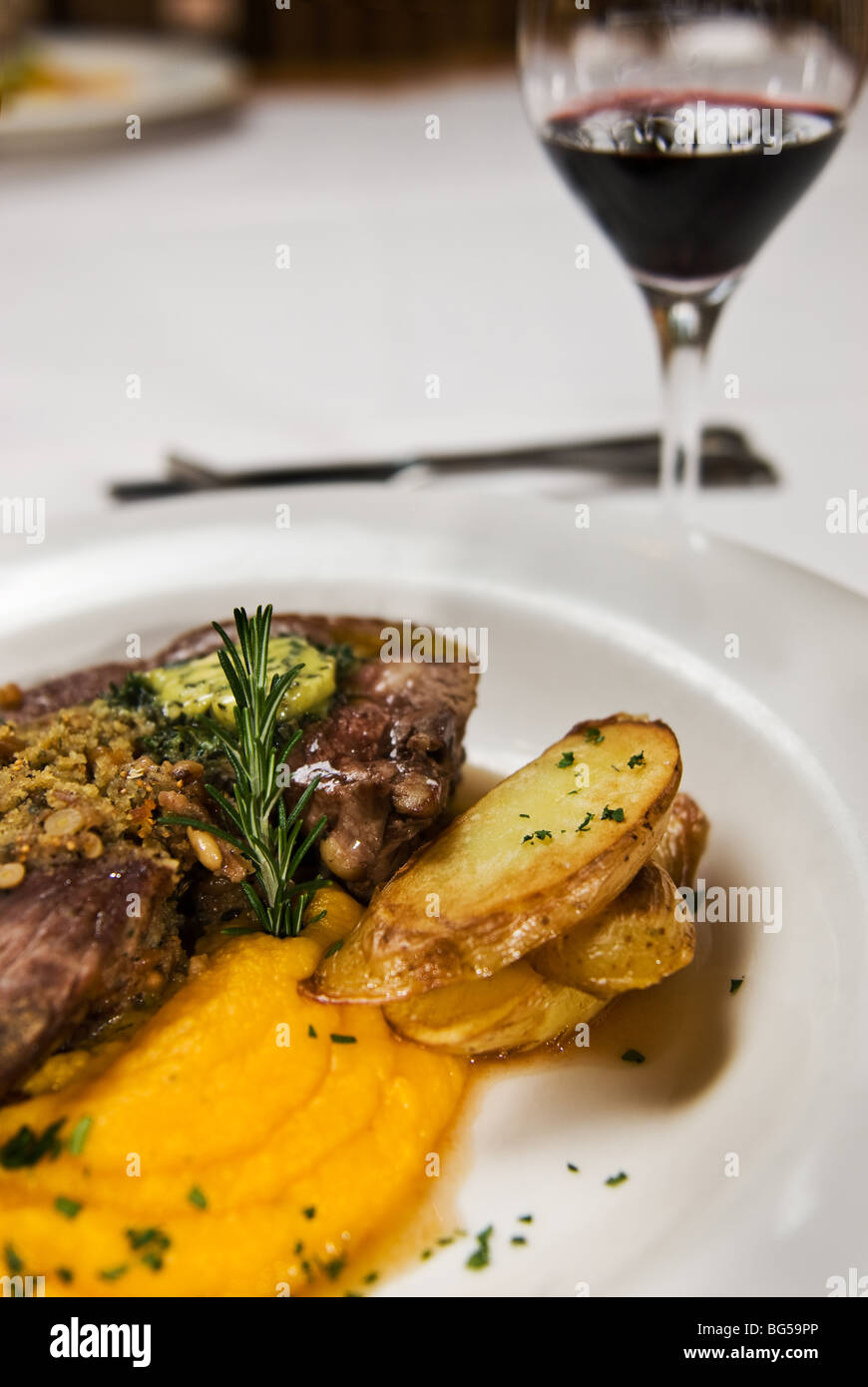 Meat, potato and pumpkin puree, served with red wine. - Stock Image