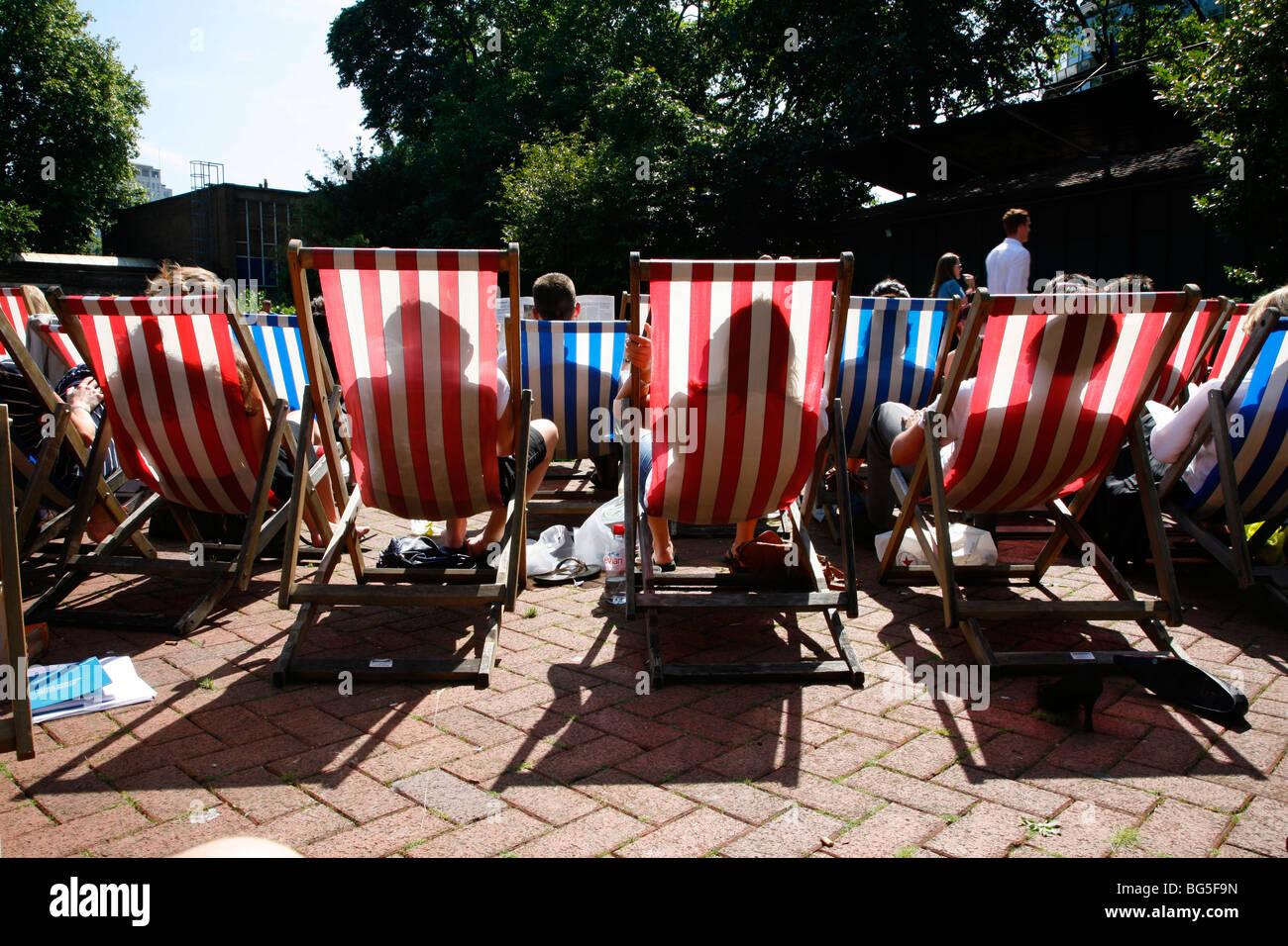 Sunbathing in deckchairs in Victoria Embankment Gardens, Charing Cross, London, UK - Stock Image