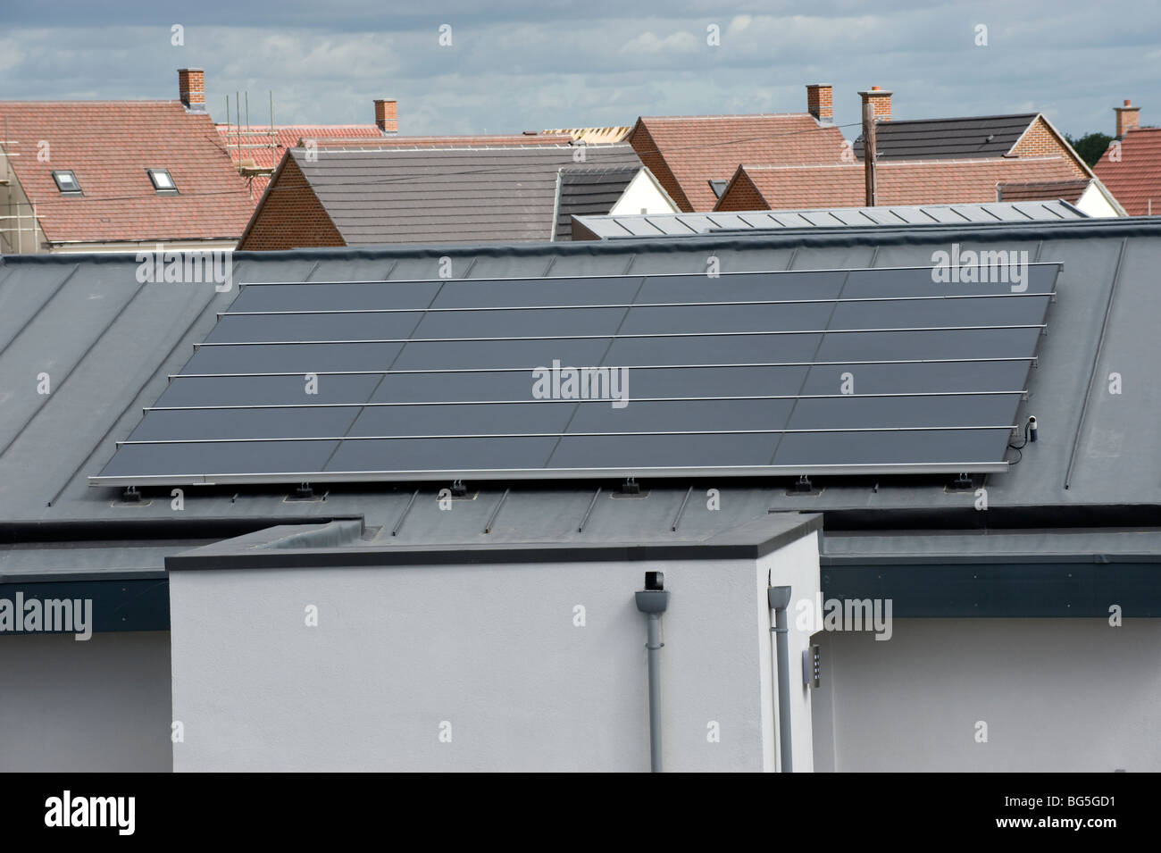 Roof-mounted photo voltaic solar panels on a new housing estate - Stock Image