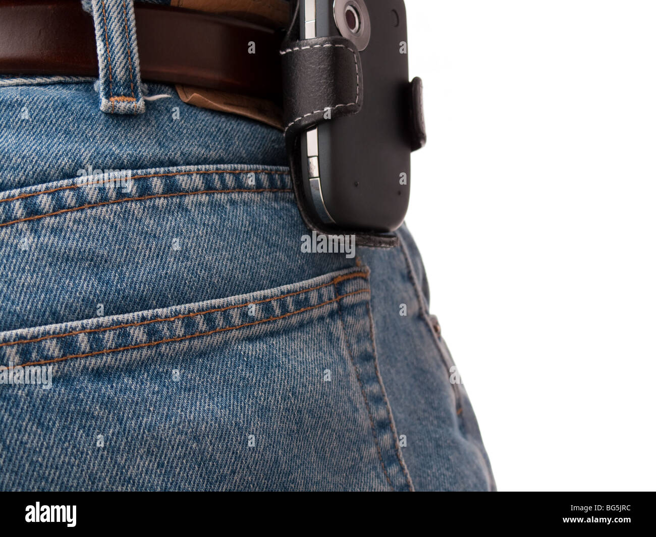 A PDA (Windows Mobile device) in a holster, attached to a belt of an IT worker, wearing jeans, shot from behind. - Stock Image