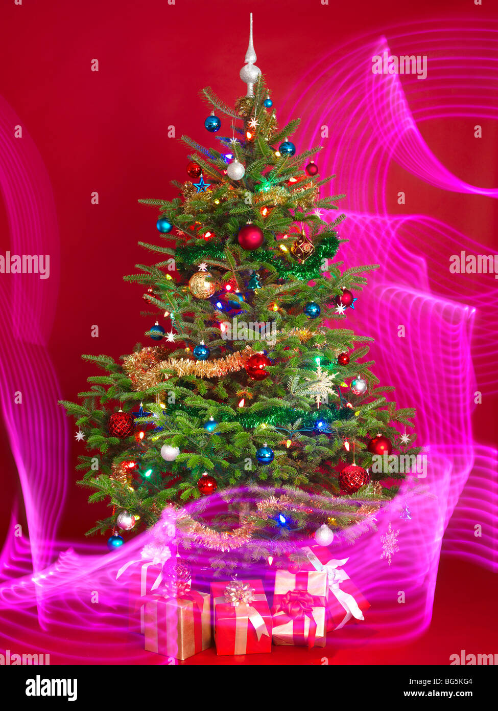 Decorated Christmas tree with purple lighting effects around it Stock Photo