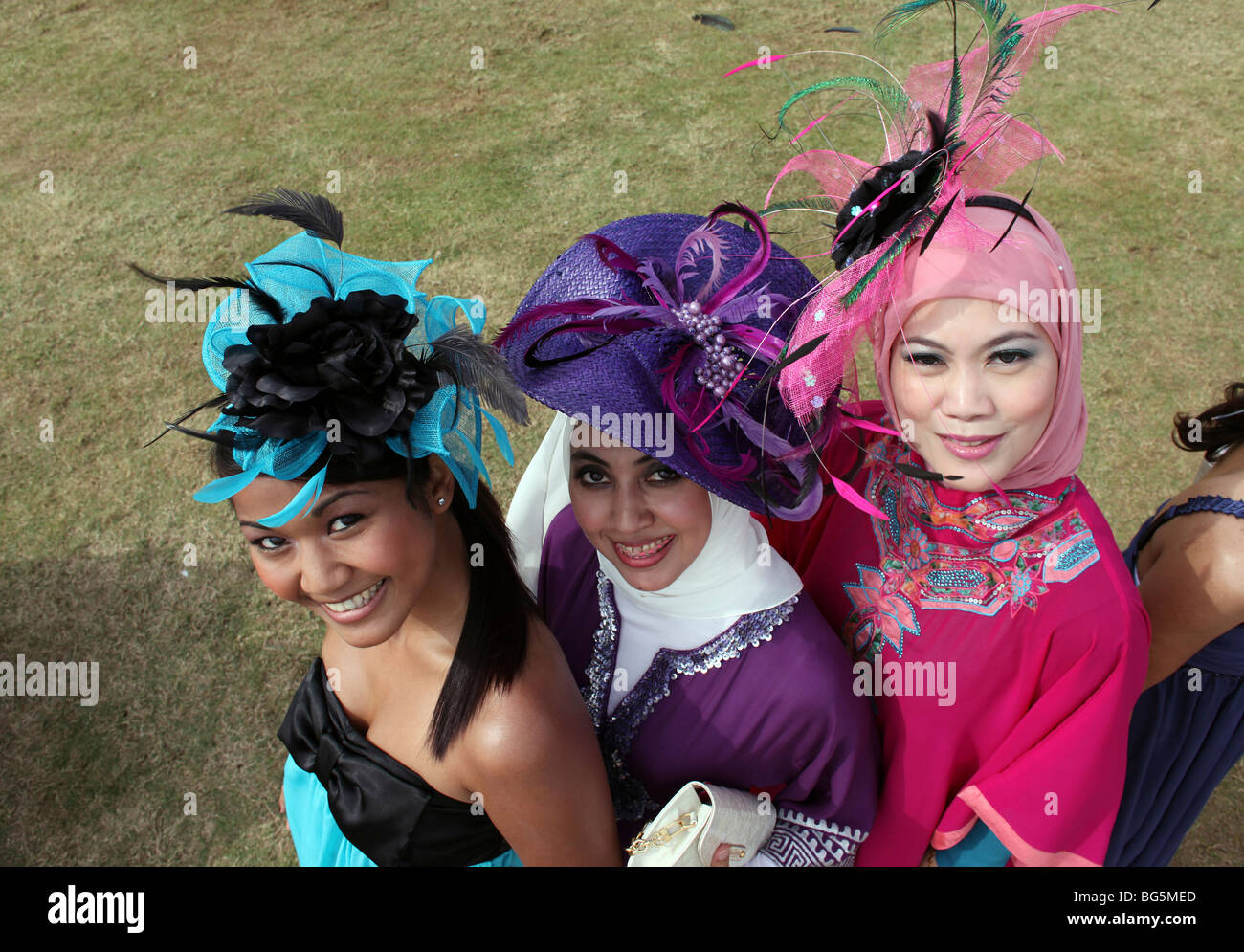 Elegantly dressed women wearing hats during a horse race, Dubai, United Arab Emirates - Stock Image