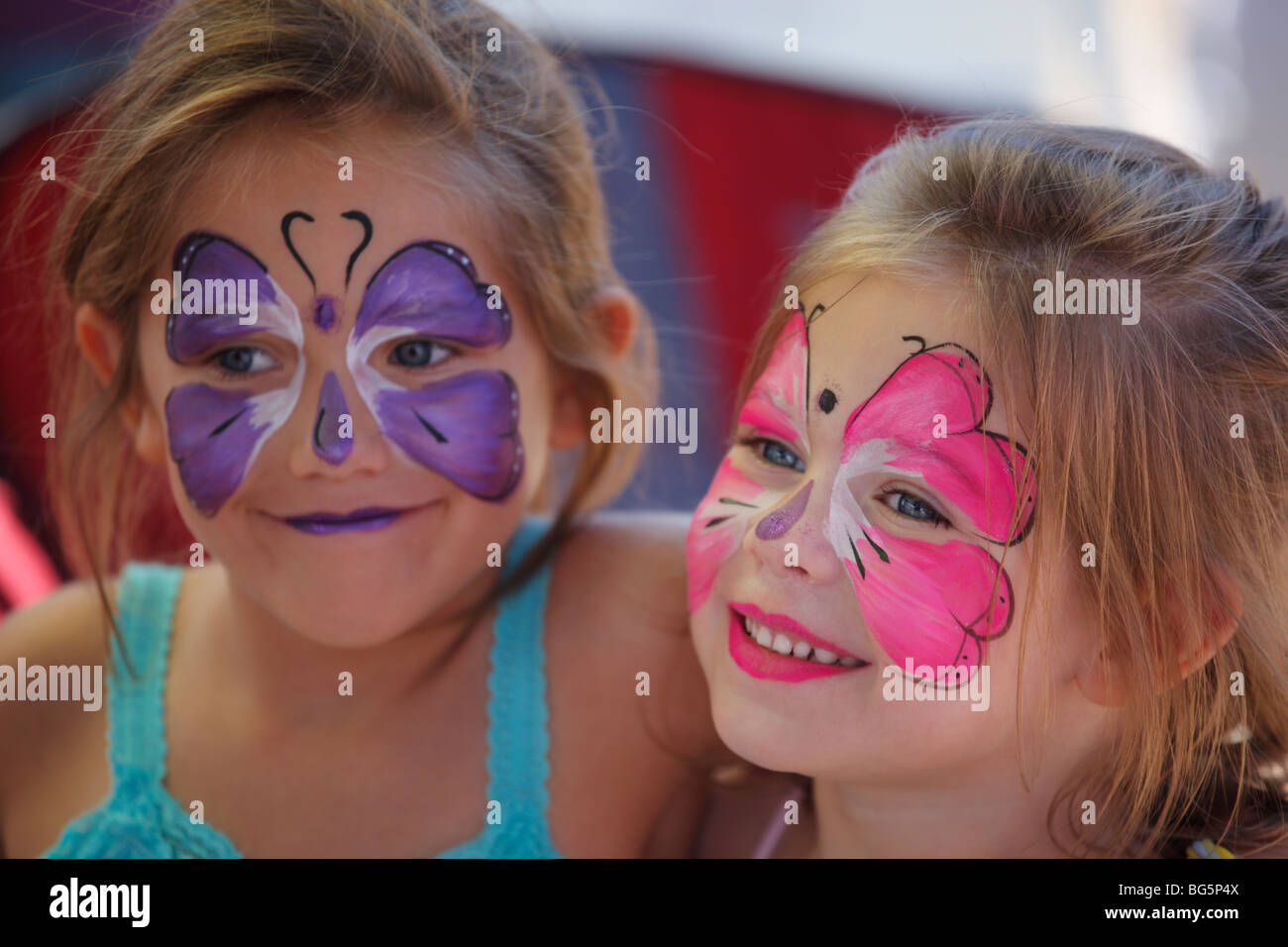 Two young girls with painted faces - Stock Image