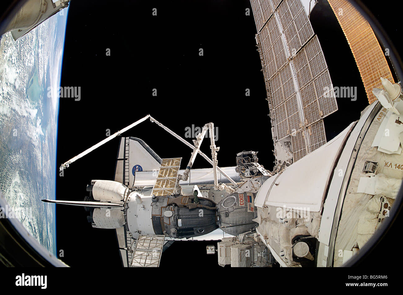 A docked Russian Soyuz spacecraft appears to rest in Space Shuttle Discovery's payload bay. - Stock Image