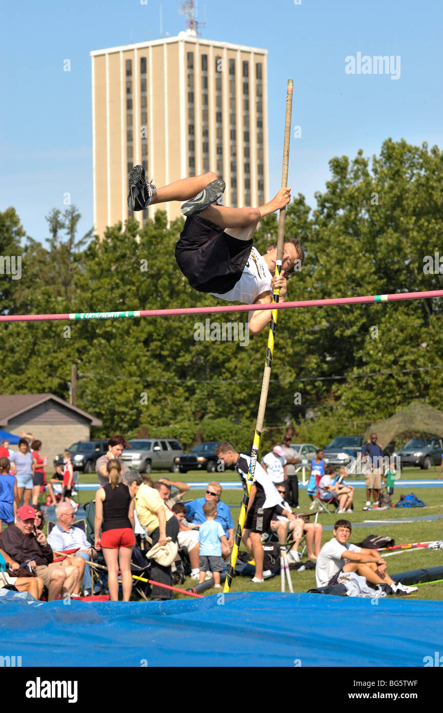 Teenage boy pole vaulter clearing the bar during the Bluegrass State Games in Lexington, Kentucky USA - Stock Image