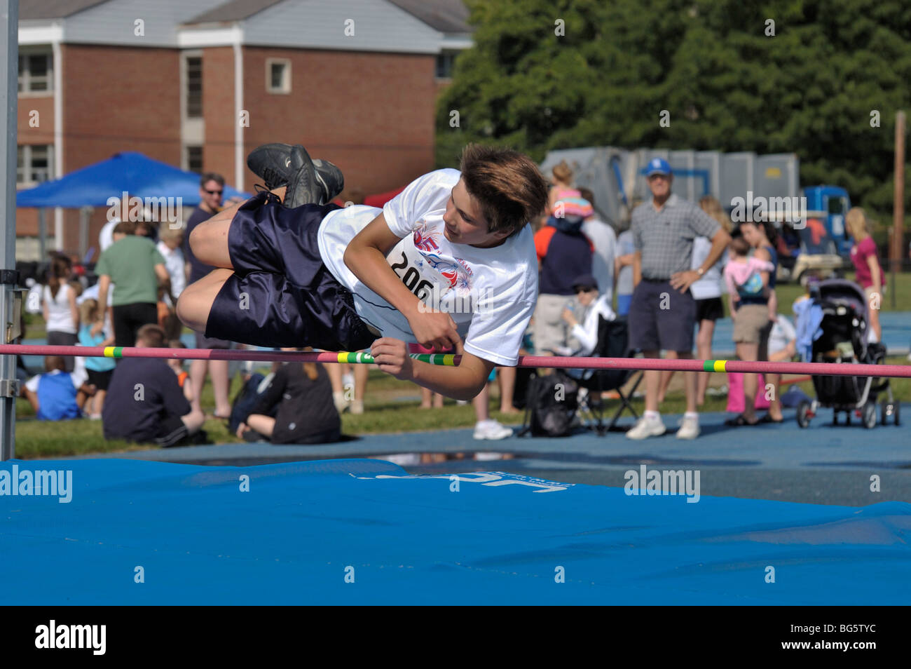 Teenage boy high jumper clearing the bar at the Track and Field competition during the Bluegrass State Games - Stock Image