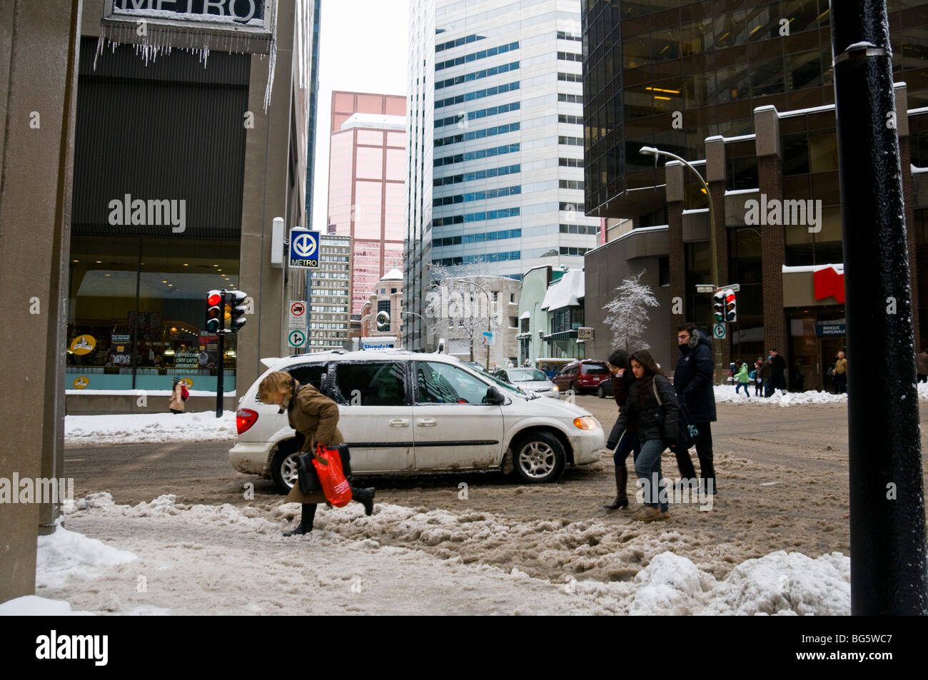 People battling with the mix of slush and snow in downtown Montreal - Stock Image