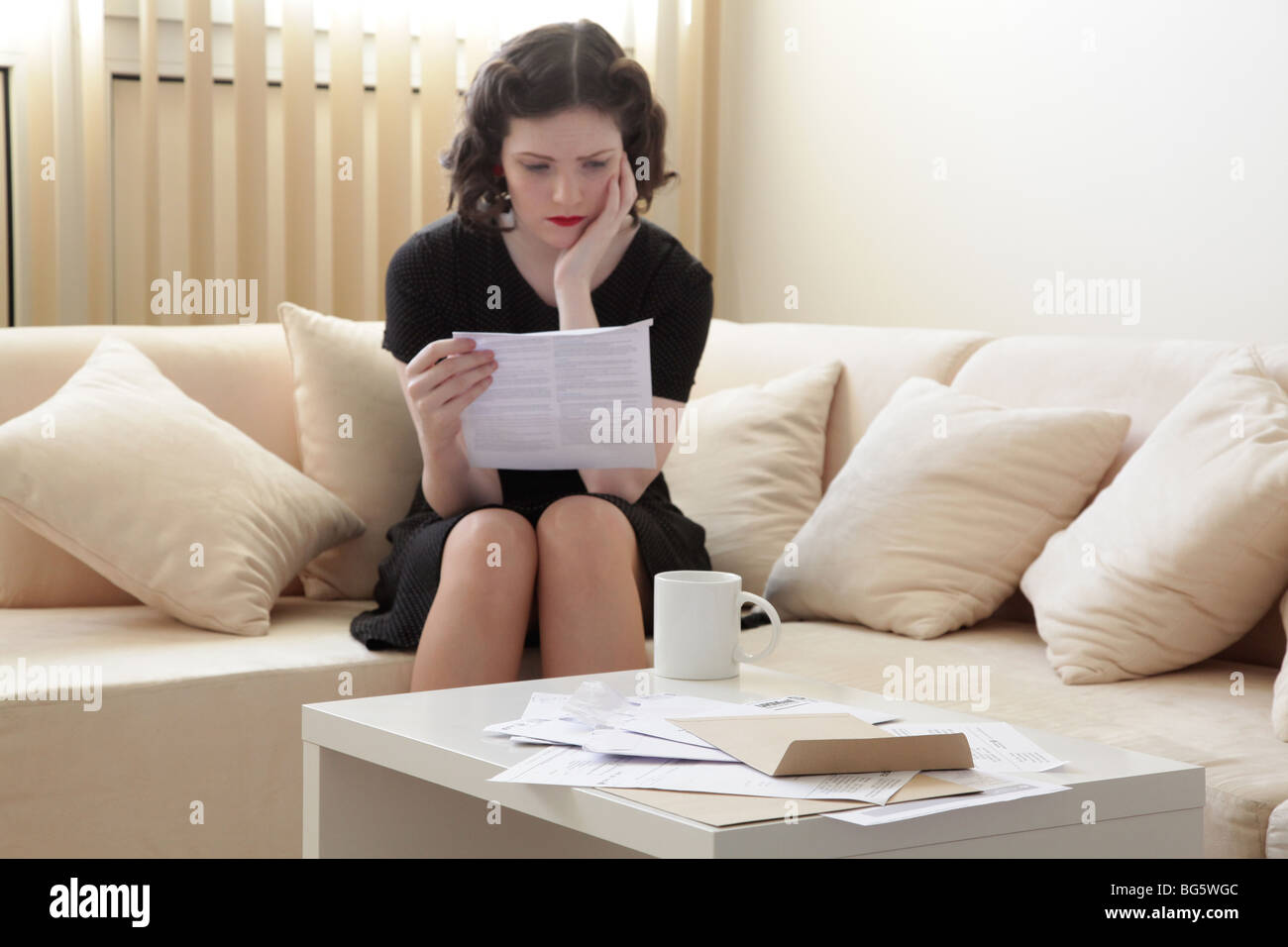 Woman looking stressed reading a bank statement - Stock Image