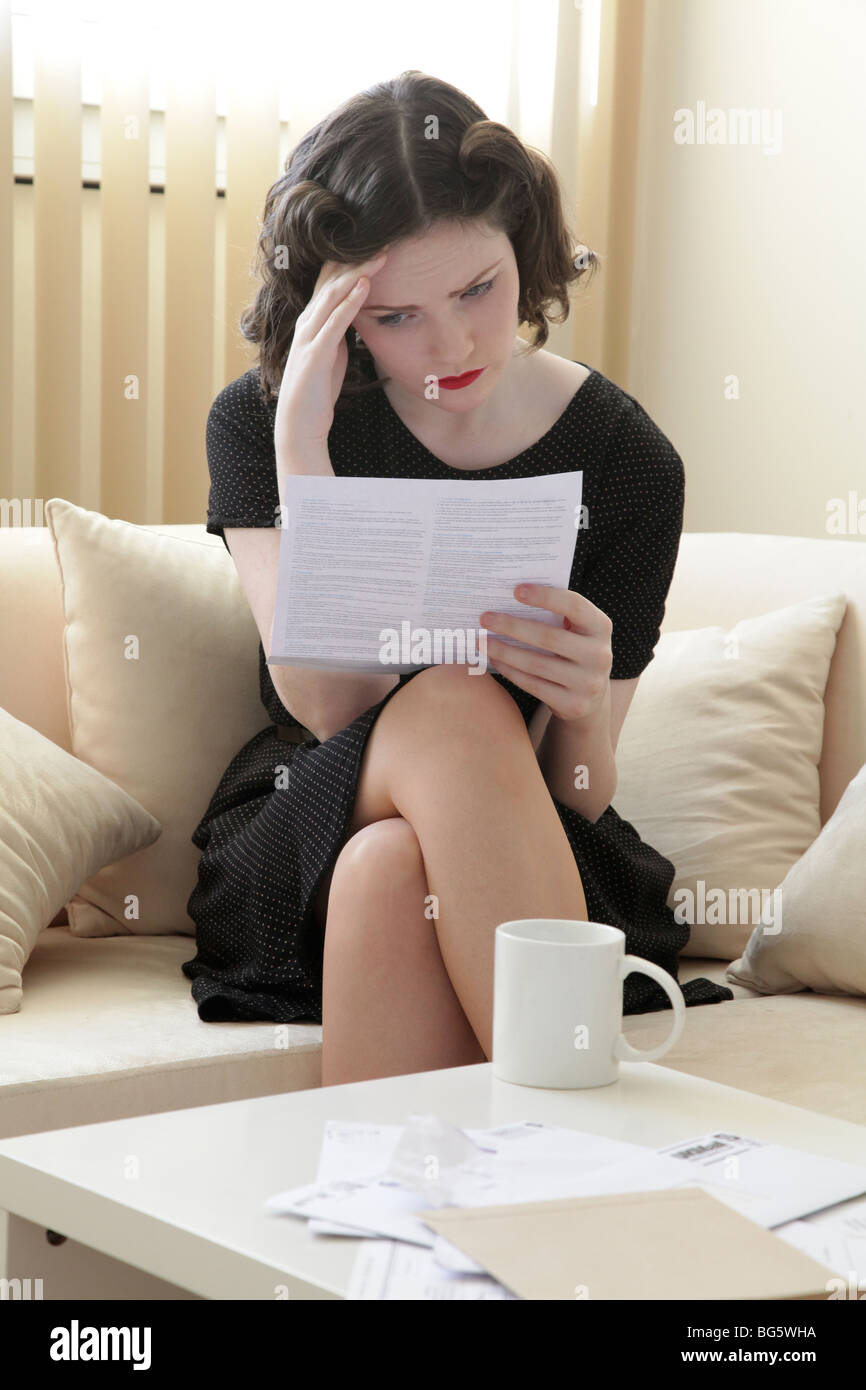 Woman looking stressed reading a bank statement Stock Photo