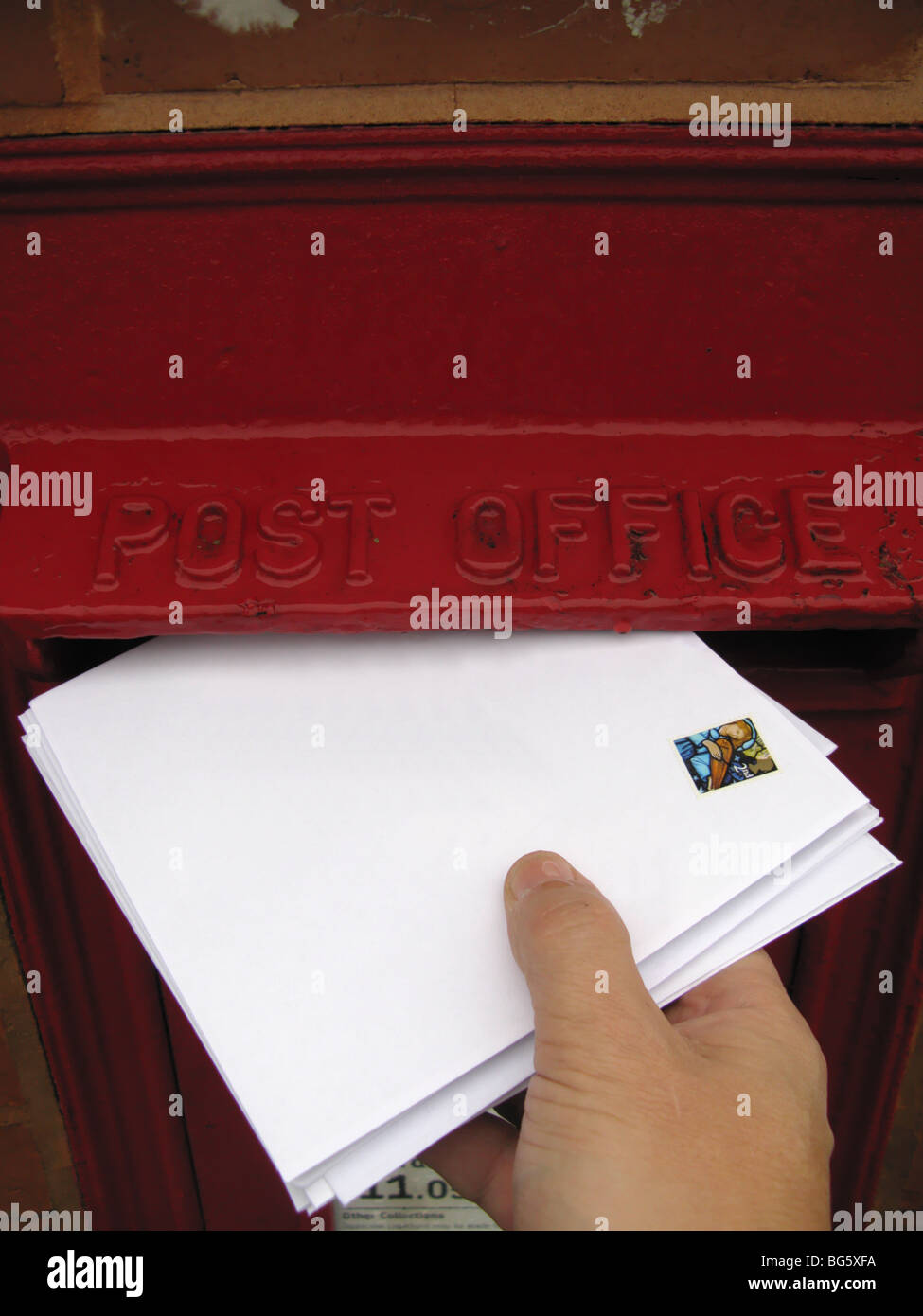 hand posting christmas cards letter in UK post box address removed - Stock Image