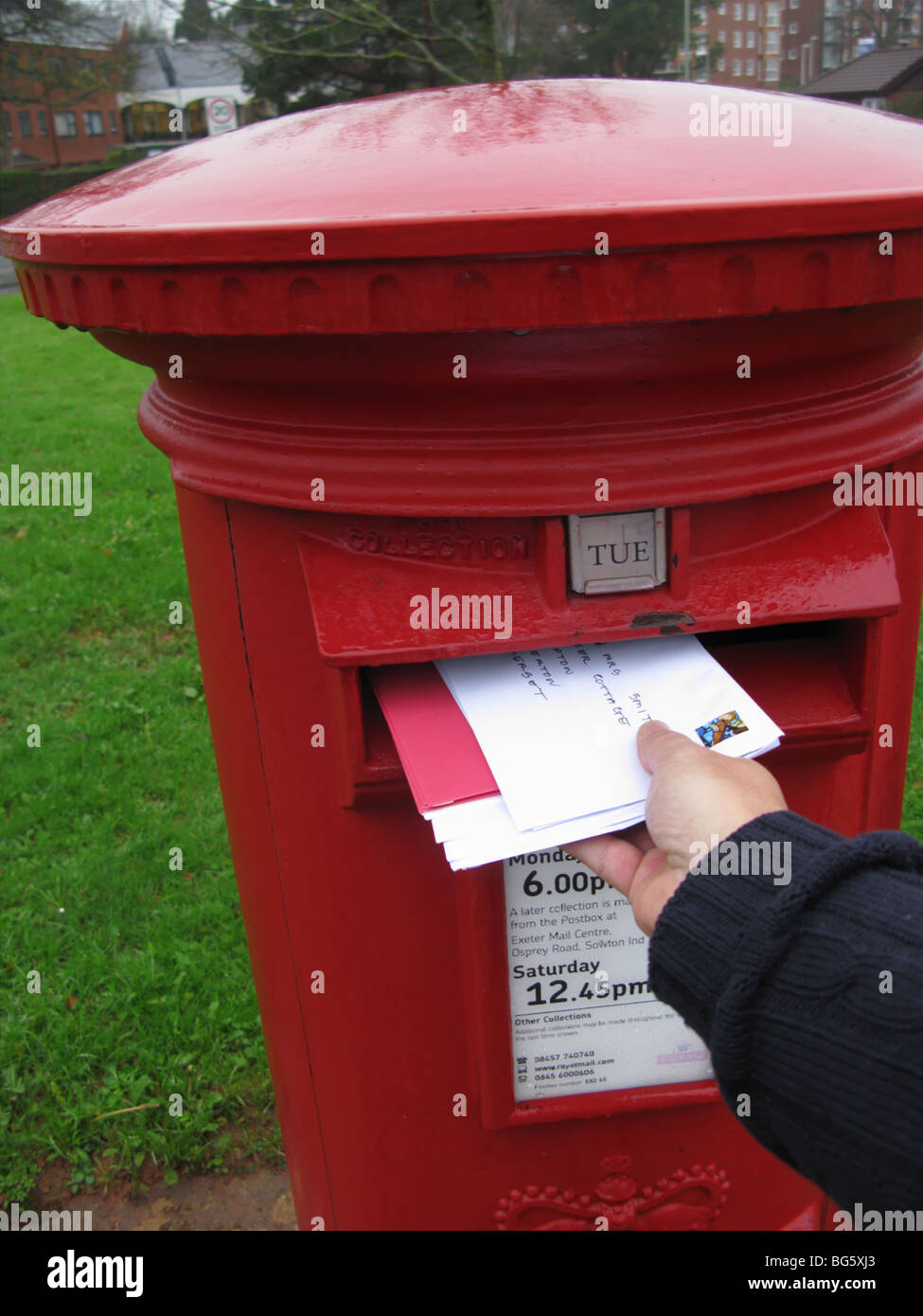 hand posting christmas cards letter in UK post box - Stock Image