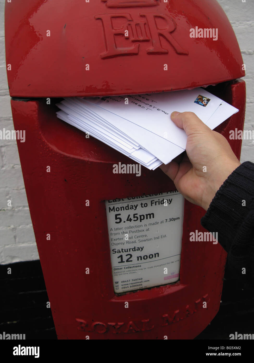 hand posting christmas cards letter in modern design UK post box - Stock Image