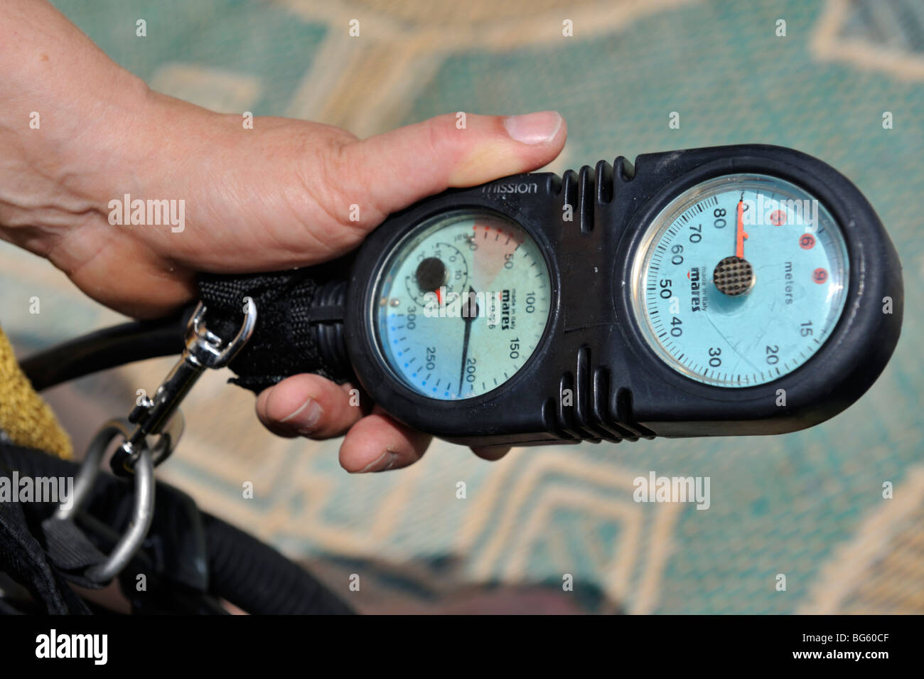 Hand holding scuba diving console with pressure and depth gauge in it - Stock Image