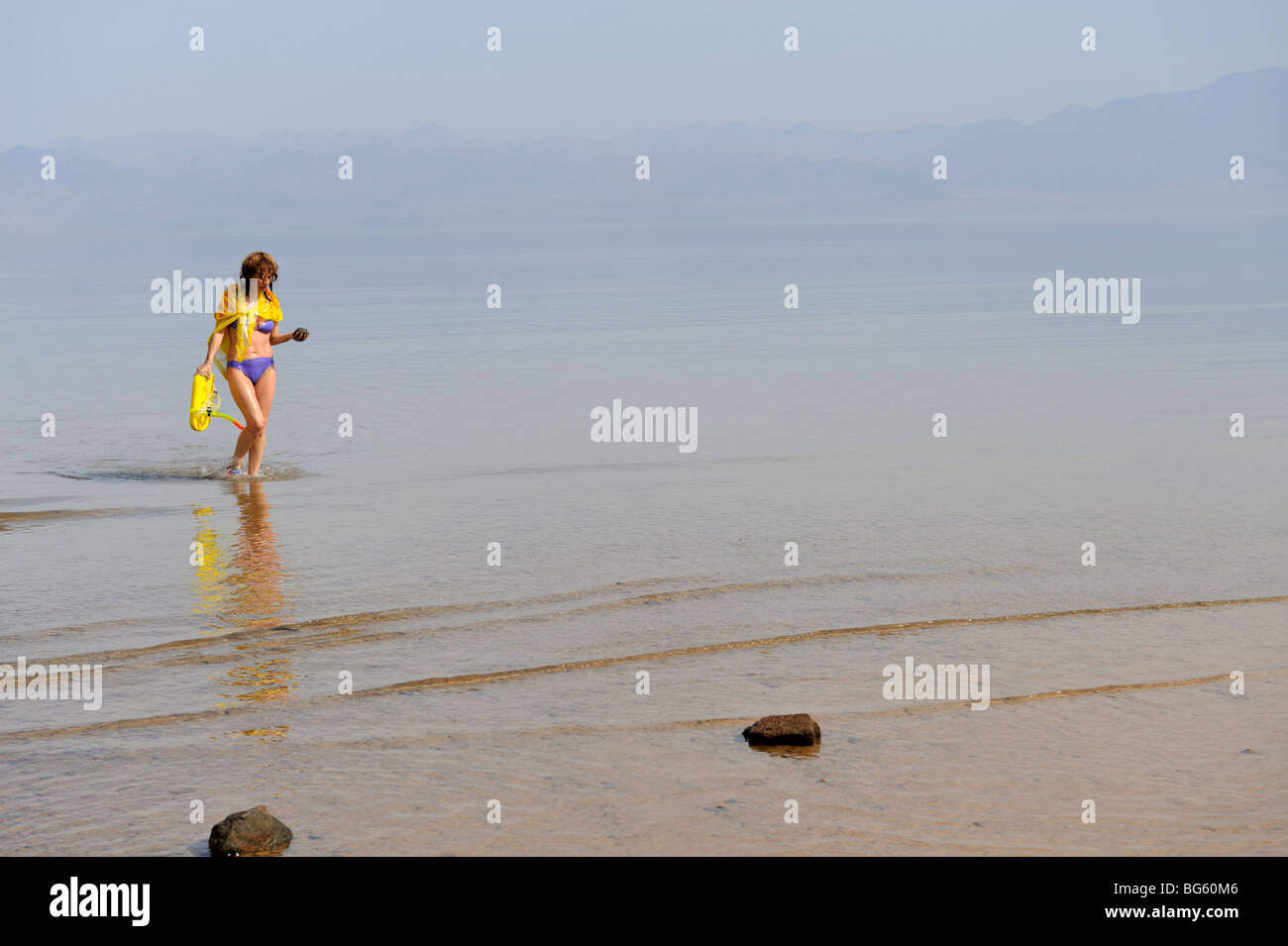 Woman in bikini walking out of sea with hazy atmosphere - Stock Image
