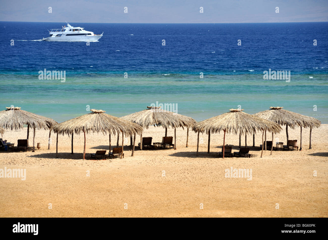 Beach, sea, thatched sunshades Nuweiba, 'Red Sea', Egypt - Stock Image