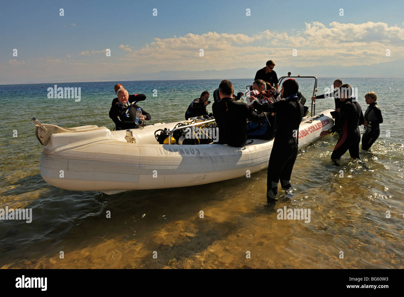Scuba divers getting into dive boat from shore, Nuweiba, 'Red Sea', Sinai, Egypt - Stock Image