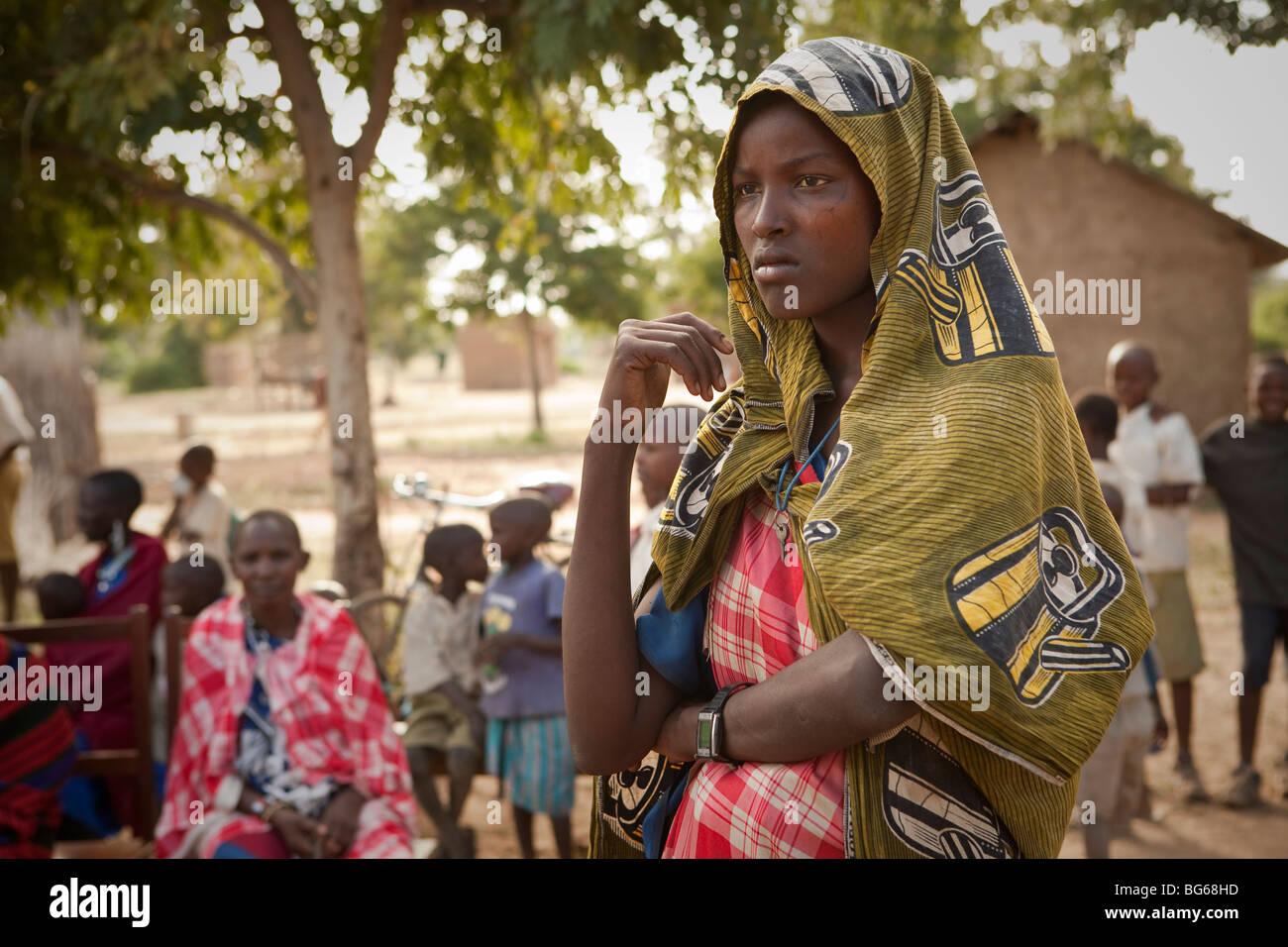 A Maasai woman in traditional dress waits outside a clinic in Kilombero Village, Manyara Region, Tanzania. - Stock Image