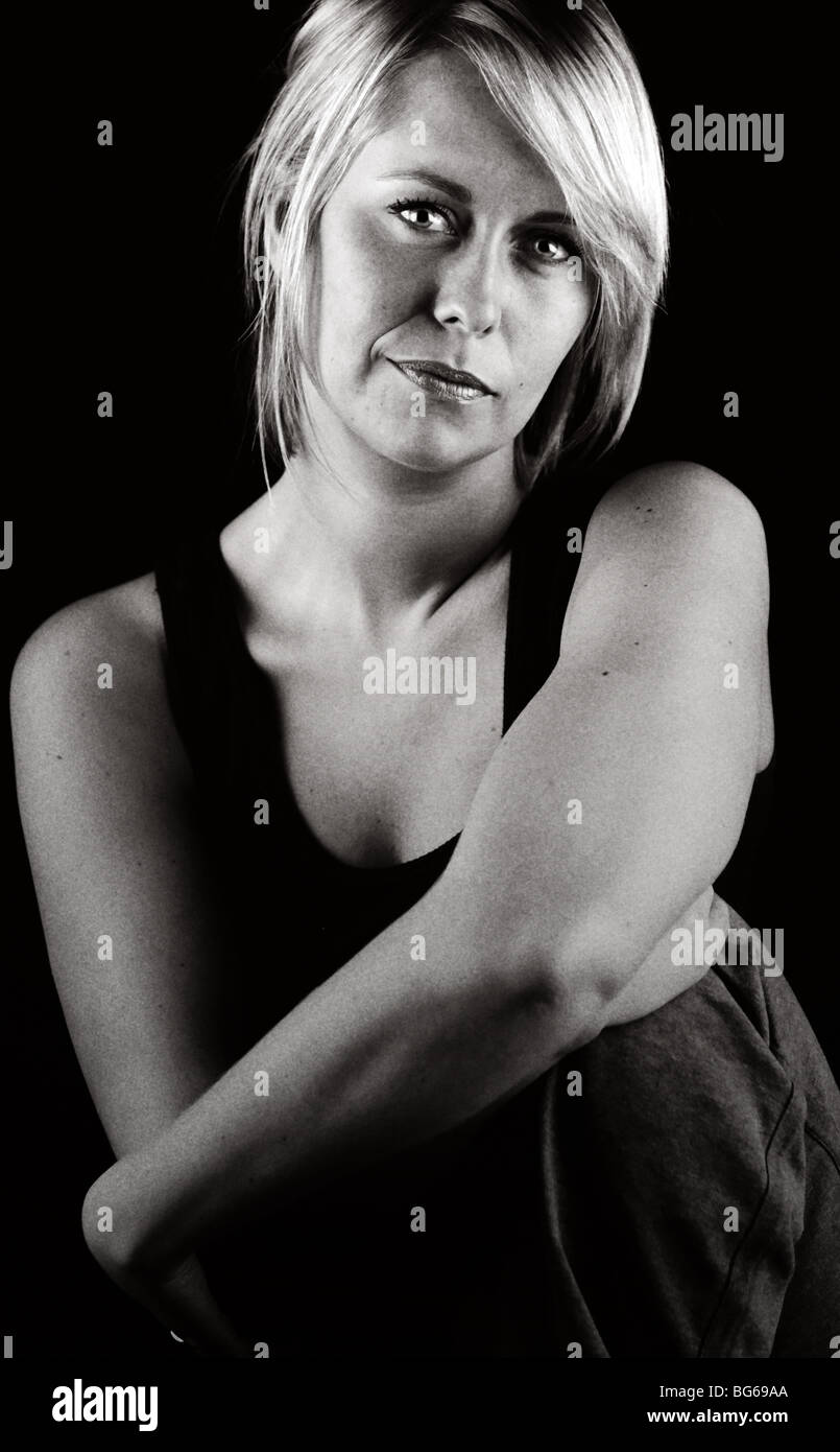 Monochromatic Shot of a Pretty Blonde Girl Looking Softly into the Camera - Stock Image